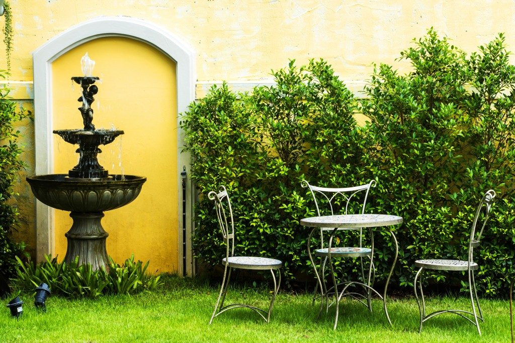 A simple garden with a fountain, a table and a chairs