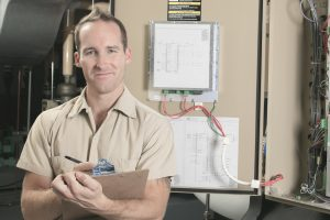 an HVAC tehnician smiling after a routine check