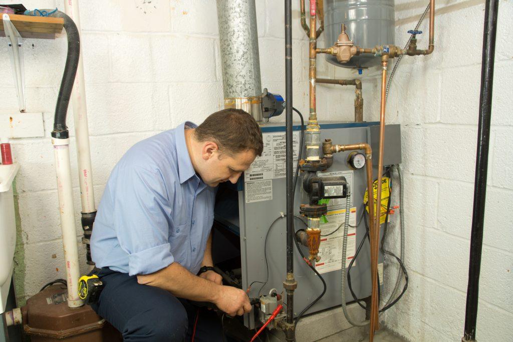 A repairman fixing a furnace