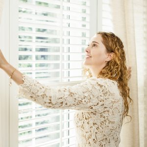 """Happy woman looking out big bright window with curtains and grills"