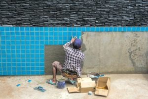 man installing tiles to new pool