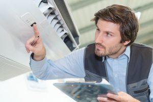 Man adjusting AC temperature