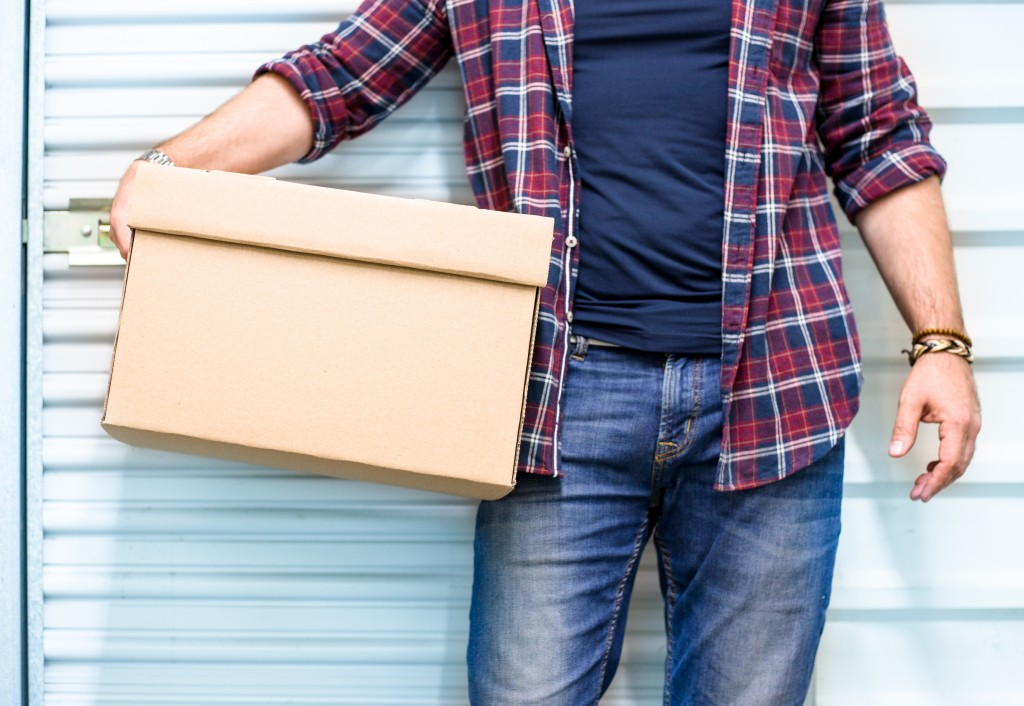 Man carrying box outside storage facility
