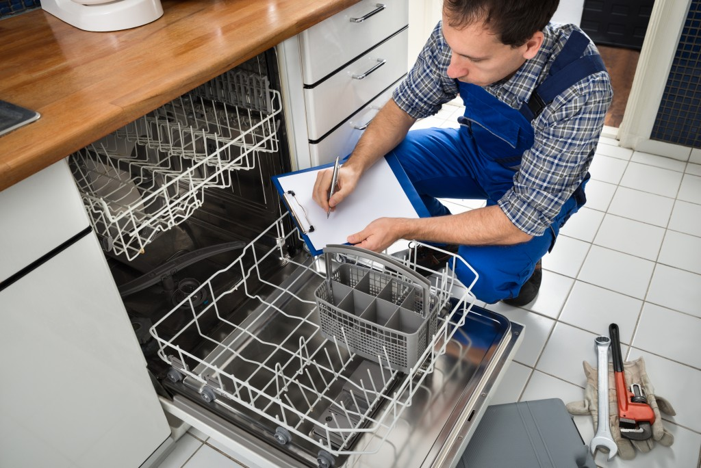 Technician maintaining dishwasher