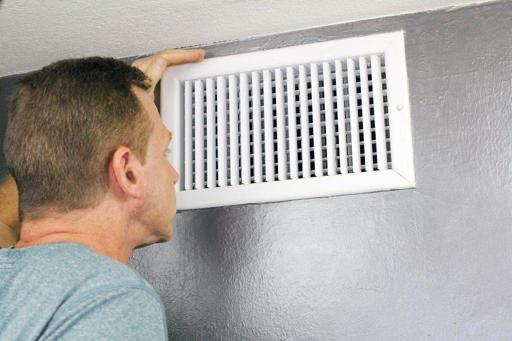 Man checking air vent
