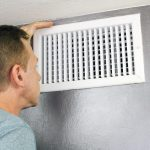 Man checking air vent