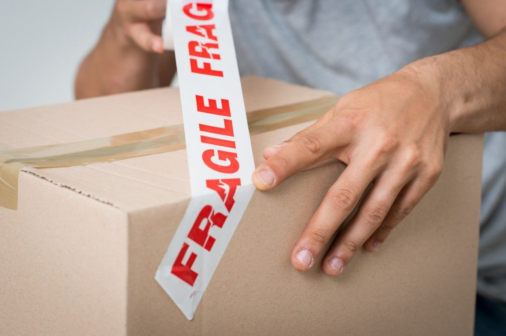man puting a fragile sign to a box