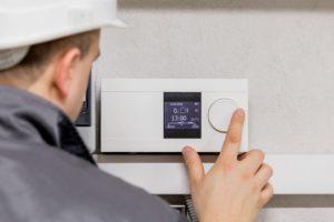 Engineer adjusting thermostat
