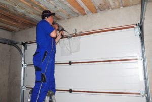 man installing garage door system