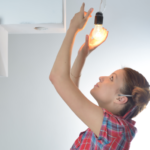 Woman changing light bulb