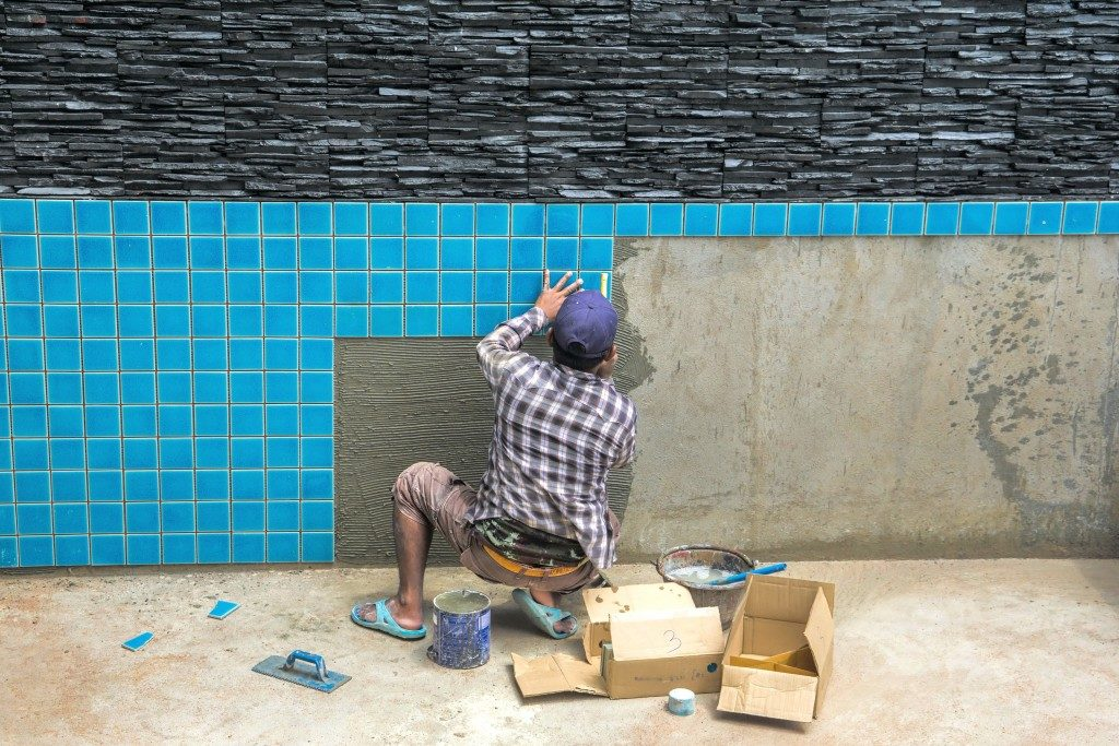 man hand while using spacer for installing tiles