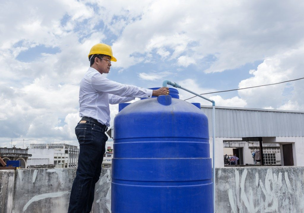 Worker inspecting the water storage tank