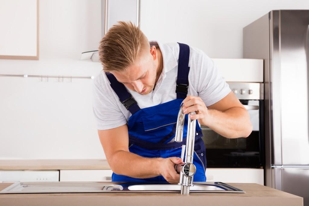 plumber installing faucet