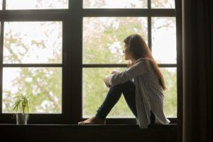 gloomy girl sitting near the window