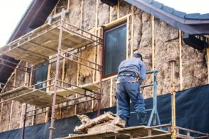 Construction worker thermally insulating house facade with glass wool
