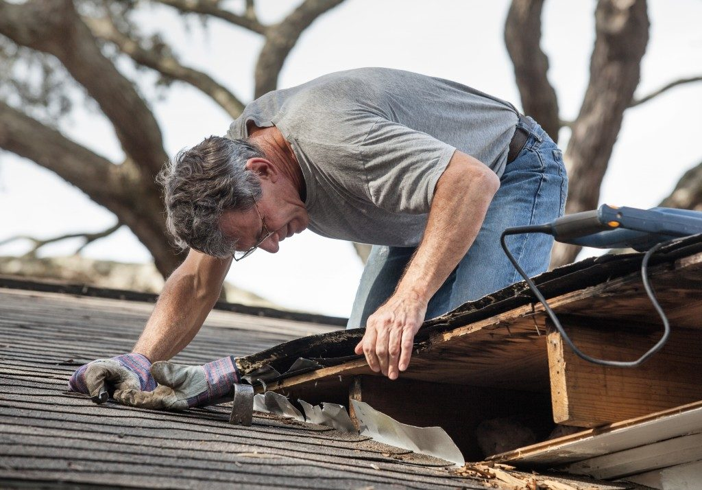 man removing rotten wood from roof