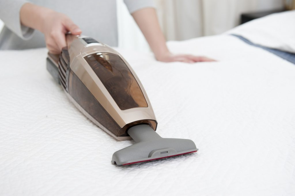 Woman vacuuming mattress