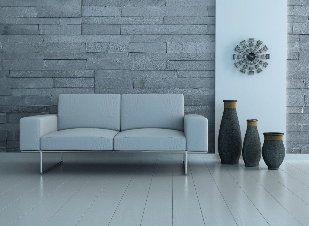 grey sofa and vases in a grey brick background
