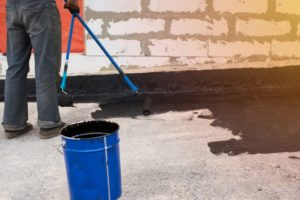 man waterproofing home foundation