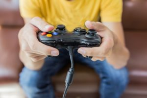 Young man holding game controller playing video games