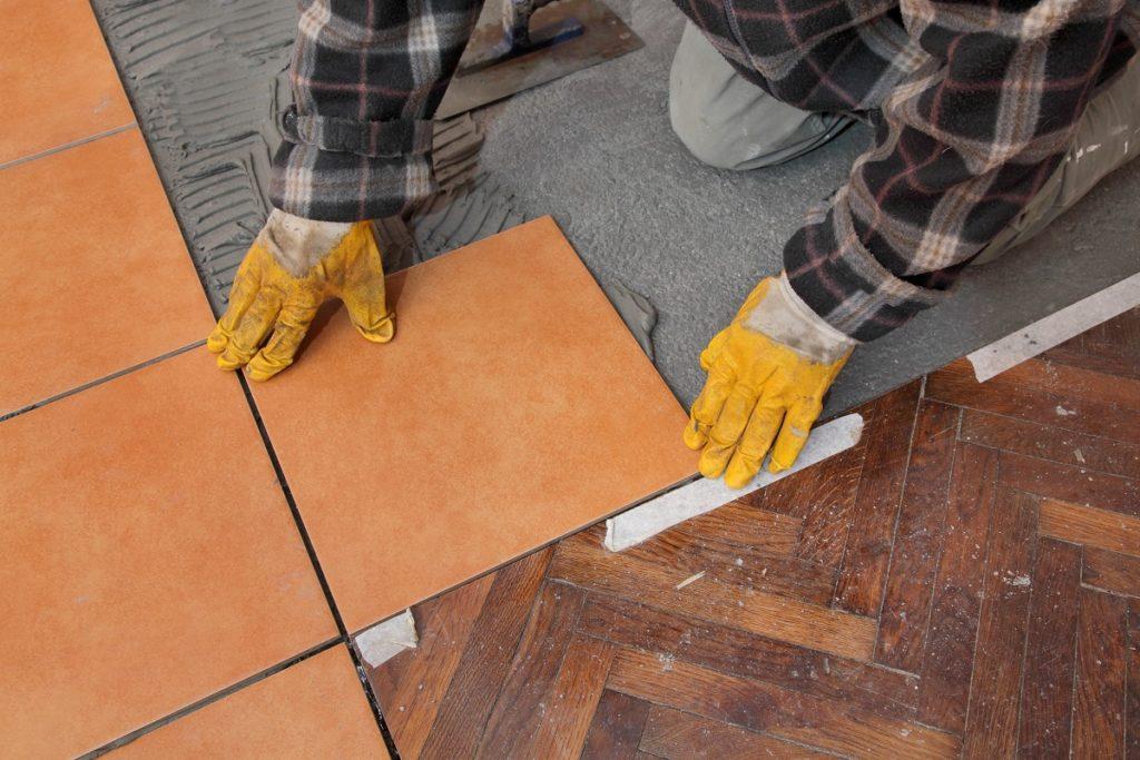 Man replacing flooring with tiles