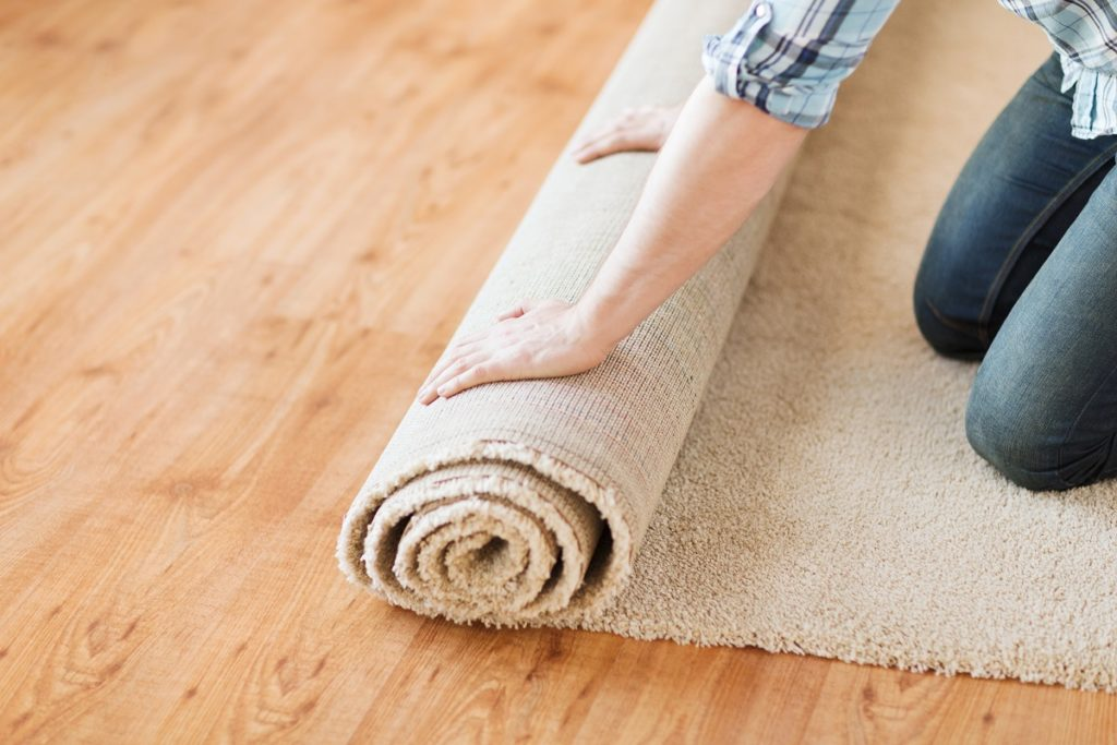 person rolling a carpet on the floor