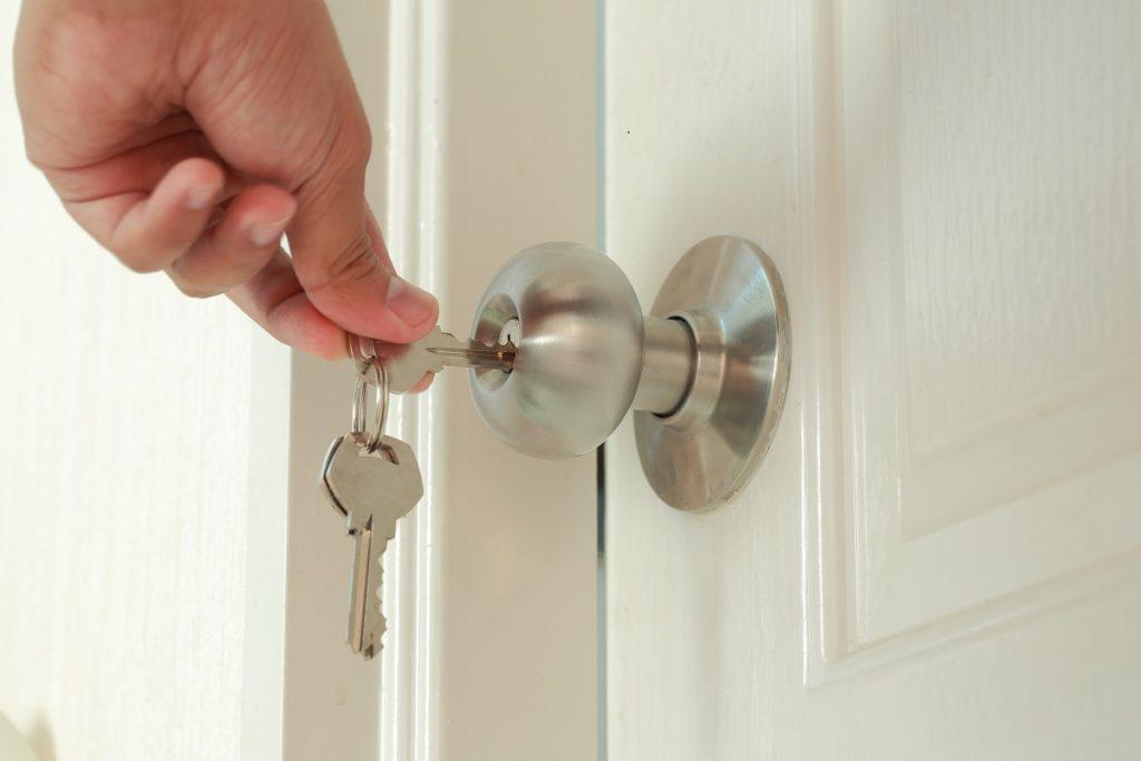 man inserting keys in door knob